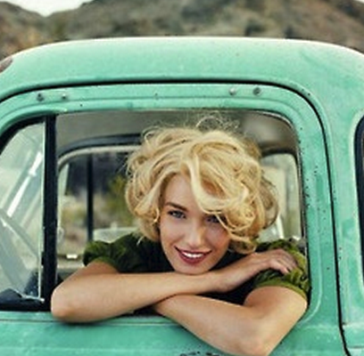 Woman Smiling In Old Junk Car.